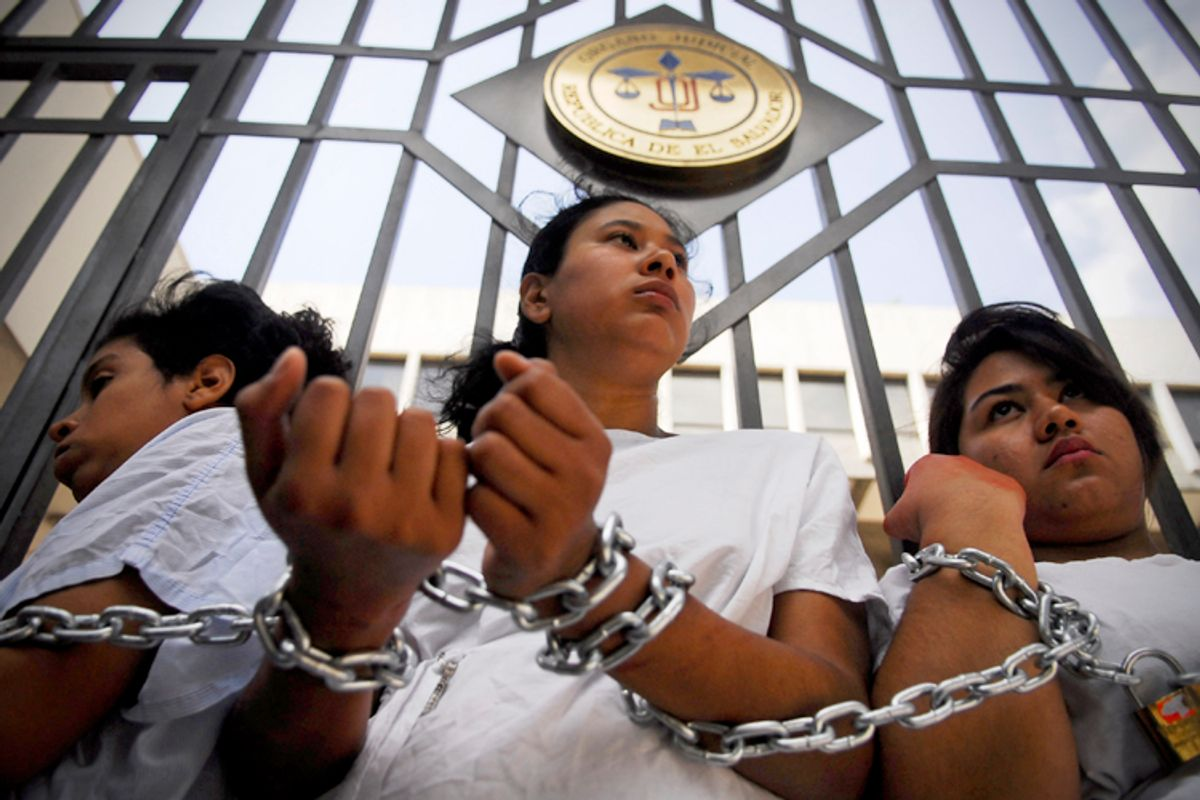 Women stand chained together outside the Supreme Court during a protest in San Salvador May 15, 2013.          (Reuters/Ulises Rodriguez)