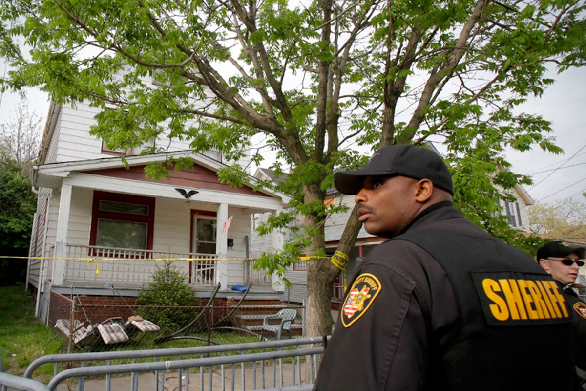 A sheriff deputy stands outside the Cleveland house where Amanda Berry, Gina DeJesus and Michelle Knight were allegedly held captive for almost a decade.           (AP/Tony Dejak)