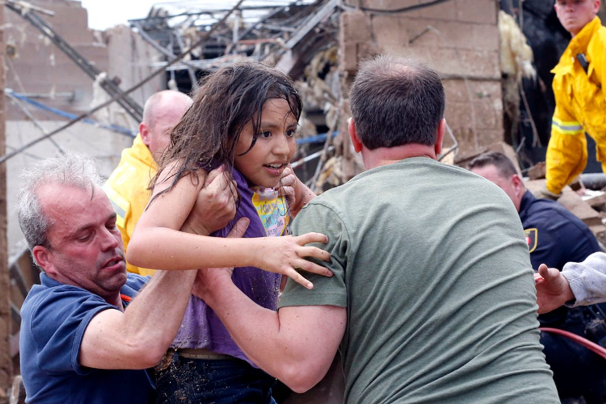 A child is pulled from the rubble of the Plaza Towers Elementary School in Moore, Okla., May 20, 2013.   (AP/Sue Ogrocki)