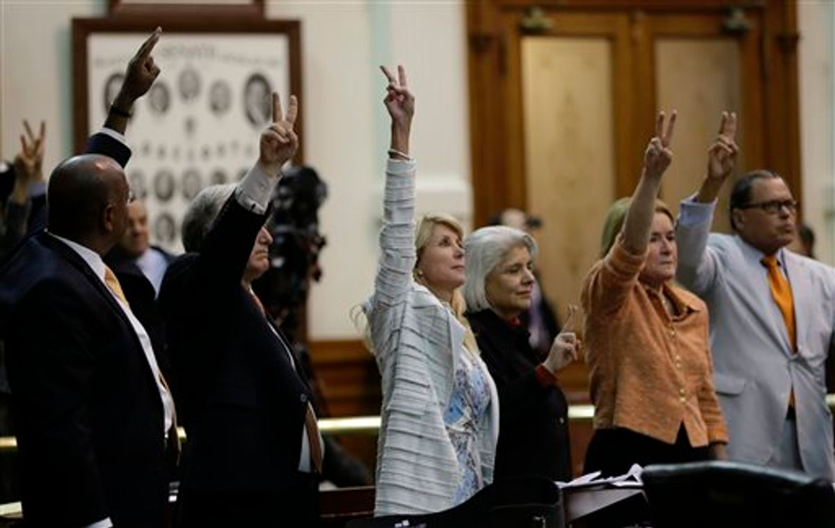 Sen. Wendy Davis, D-Fort Worth, center, who tries to  filibuster an abortion bill, hold up a no vote as time expires, Wednesday, June 26, 2013, in Austin, Texas. Amid the deafening roar of abortion rights supporters, Texas Republicans huddled around the Senate podium to pass new abortion restrictions, but whether the vote was cast before or after midnight is in dispute. If signed into law, the measures would close almost every abortion clinic in Texas.  (AP Photo/Eric Gay)              (AP)
