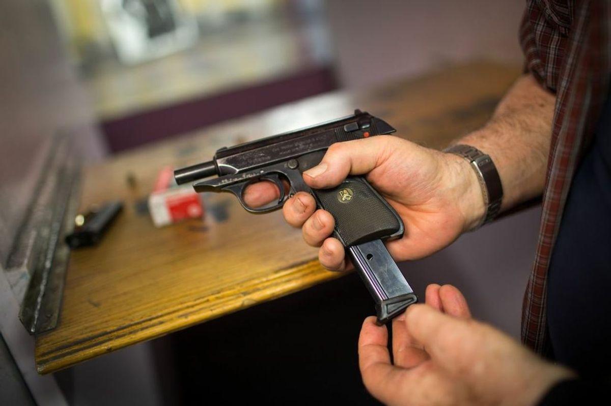A range member loads a magazine into his pistol.