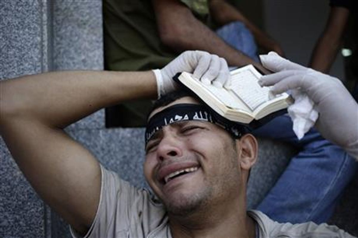 An Egyptian grieves for supporters of Egypt's ousted President Mohammed Morsi, who were killed in overnight clashes with security forces, at a field hospital in Nasr City, Cairo, Saturday, July 27, 2013. Clashes erupted early Saturday in Cairo between security forces and supporters of Morsi, killing scores of protesters and overwhelming field hospitals with the wounded. (AP Photo/Hassan Ammar)