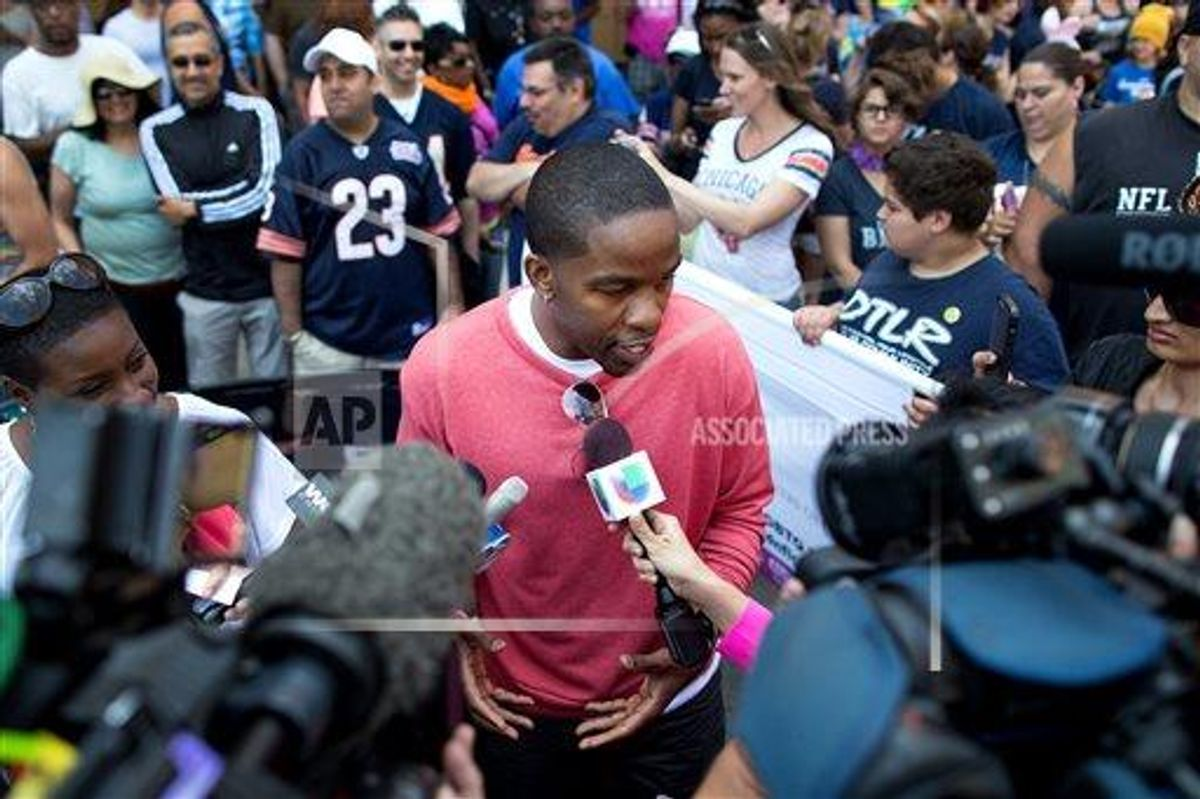 Former NFL football player Wade Davis speaks to reporters prior to the Chicago Gay Pride Parade, Sunday, June 30, 2013.      (AP Photo/Scott Eisen)