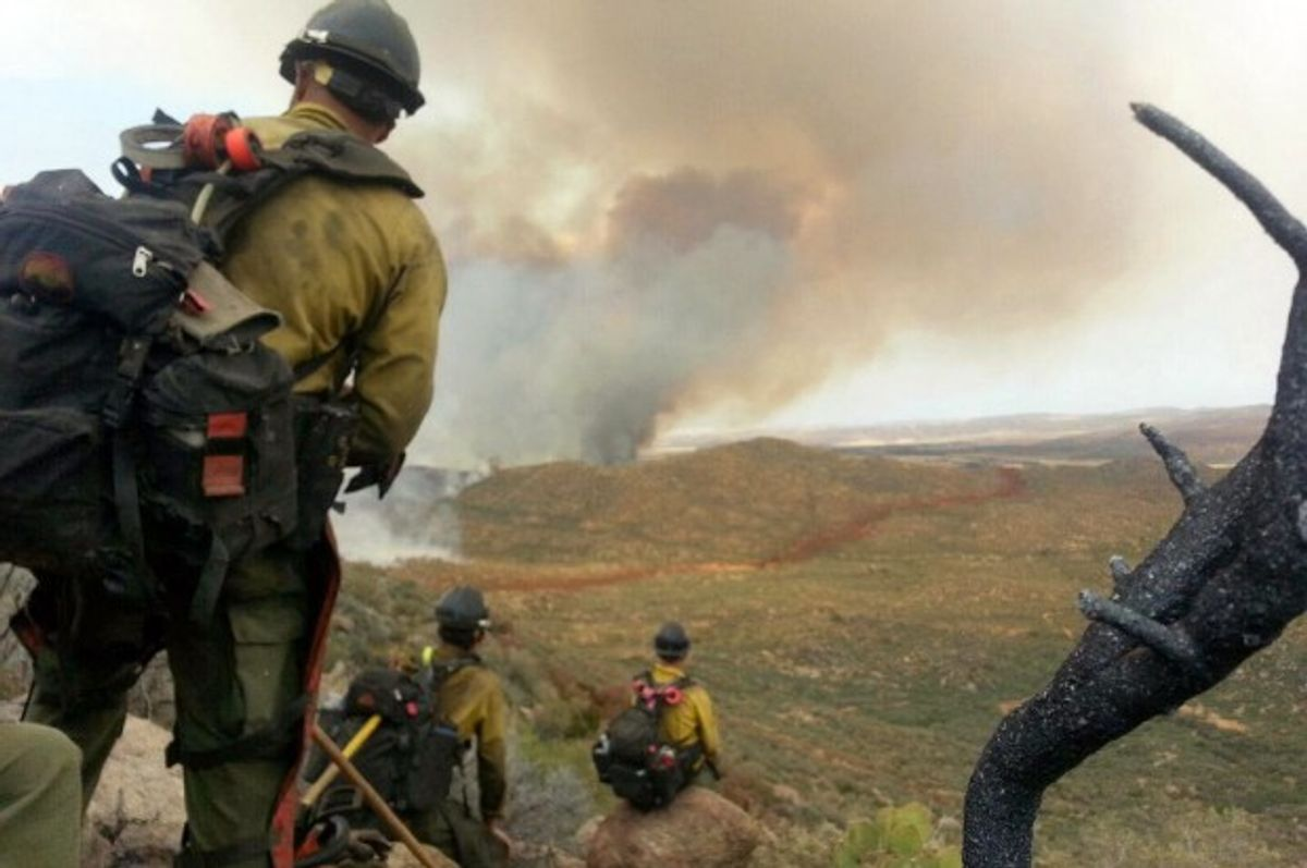 In this photo shot by firefighter Andrew Ashcraft, members of the Granite Mountain Hotshots watch a growing wildfire that later swept over and killed the crew of 19 firefighters near Yarnell, Ariz., Sunday, June 30, 2013.  (AP/Courtesy of Juliann Ashcraft)