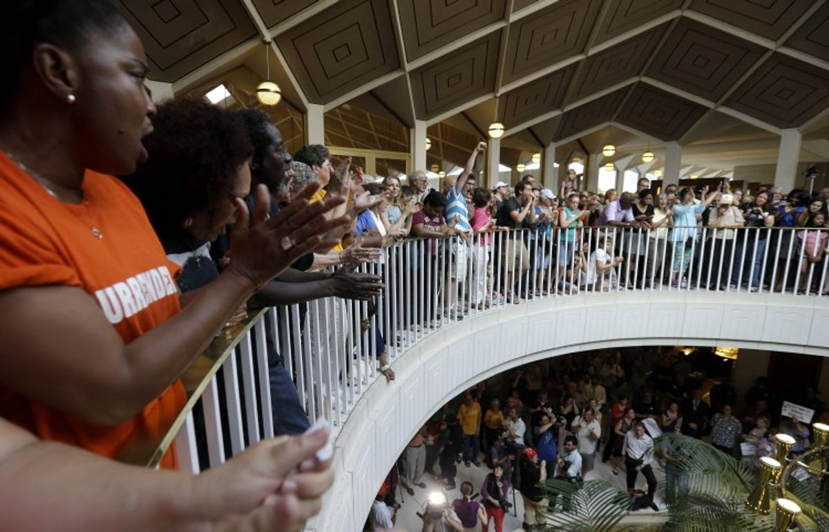 Protestors gather around the balcony overlooking the House and Senate floors during a demonstration at the state legislature in Raleigh, N.C., Monday, June 17, 2013. (AP)