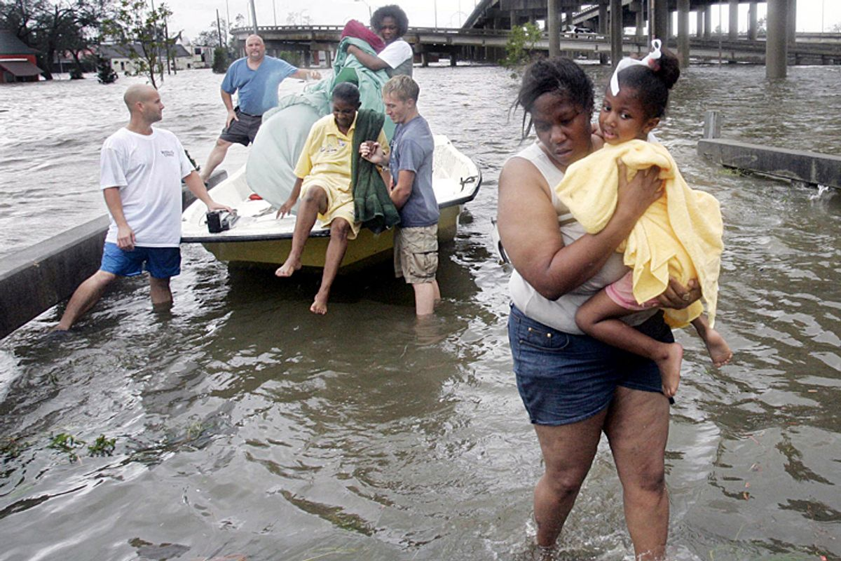Shante Gruld carries Janeka Garner, 5, to safety after they were rescued from their flooded home by boat in New Orleans, Aug. 29, 2005.       (AP/Eric Gay)