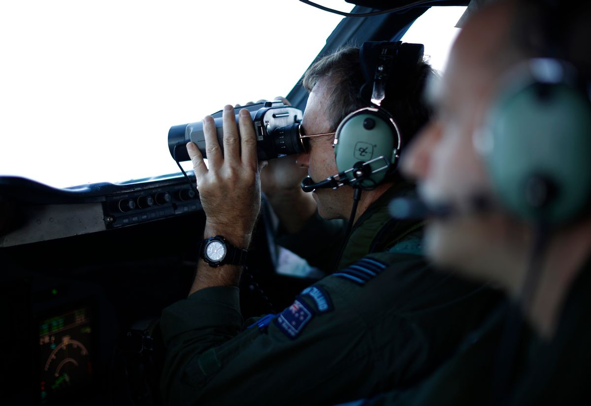Wing Commander Rob Shearer looks through binoculars on the flight deck of a Royal New Zealand Air Force P-3K2 Orion aircraft searching for missing Malaysian Airlines flight 370 over the southern Indian Ocean, March 29, 2014.  (AP Photo/Jason Reed, Pool)