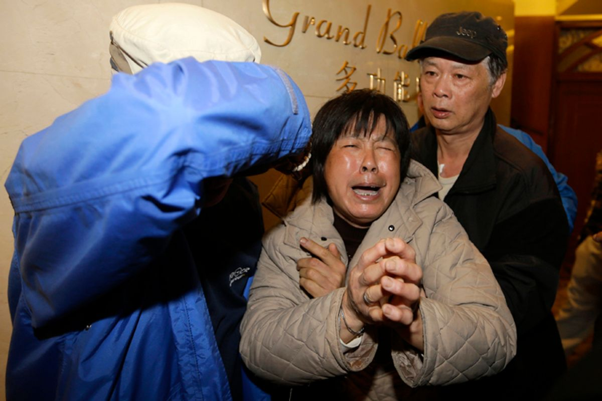 A family member of a passenger aboard Malaysia Airlines MH370 cries after watching a television broadcast of a news conference, at the Lido hotel in Beijing March 24, 2014.          (Reuters/Jason Lee)