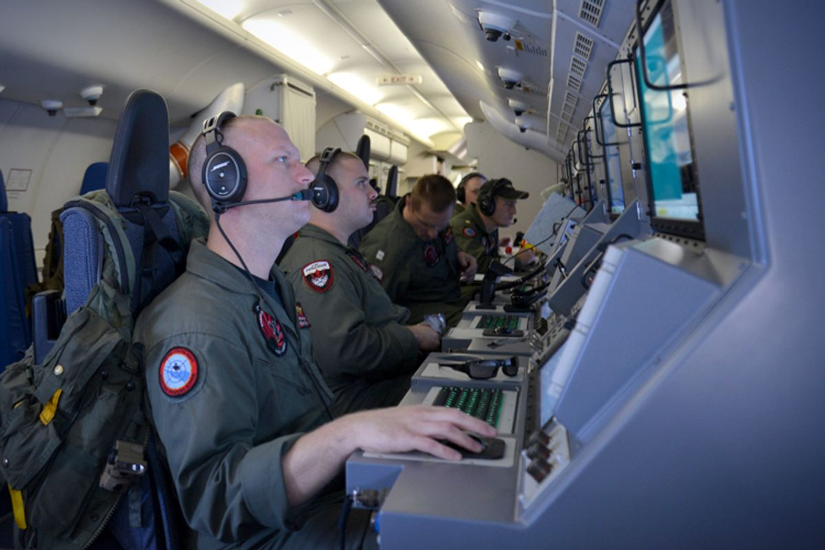 Crew members on board aircraft P-8A Poseidon assist in search and rescue operations for Malaysia Airlines flight MH370 in the Indian Ocean, March 16, 2014.      (AP/Eric A. Pastor)