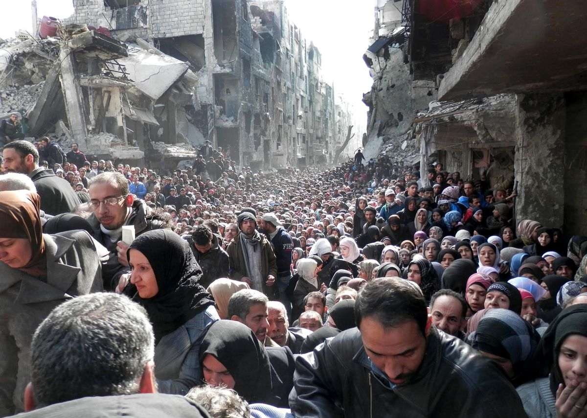 """FILE -- In this Jan. 31, 2014, file photo, released by the United Nations Relief and Works Agency for Palestine Refugees in the Near East (UNRWA), shows residents of the besieged Palestinian camp of Yarmouk, queuing to receive food supplies, in Damascus, Syria. In one besieged neighborhood after another, weary rebels have turned over their weapons to the Syrian government in exchange for an easing of suffocating blockades that have prevented food, medicine and other staples from reaching civilians trapped inside. The government touts the truces as part of its program of """"national reconciliation"""" to end Syria's crisis, which has killed more than 140,000 people since March 2011. (AP Photo/UNRWA, File) (AP)"""