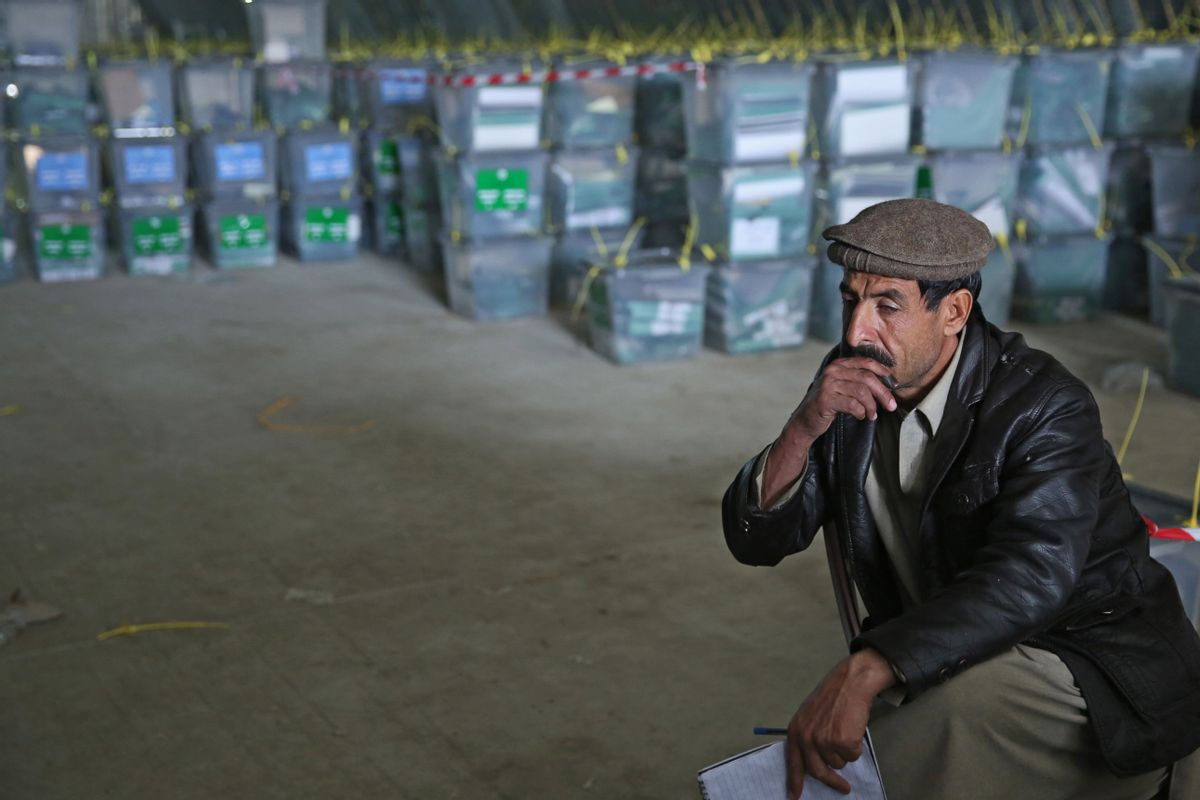 An Afghan election worker rests while working with ballot boxes at a warehouse of the Independent Elections Commission warehouse in Kabul, Afghanistan, Sunday, April 6, 2014. Trucks and donkeys loaded with ballot boxes made their way to counting centers on Sunday as Afghans and the international community sighed with relief that national elections were held without major violence despite a Taliban threat. (AP Photo/Massoud Hossaini) (AP)