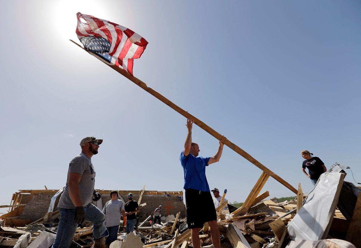 Justin Shaw, left, helps Nick Conway erect a flag pole at his home that was destroyed by a tornado, Monday, April 28, 2014, in Vilonia, Ark. (AP Photo/Eric Gay) (AP)