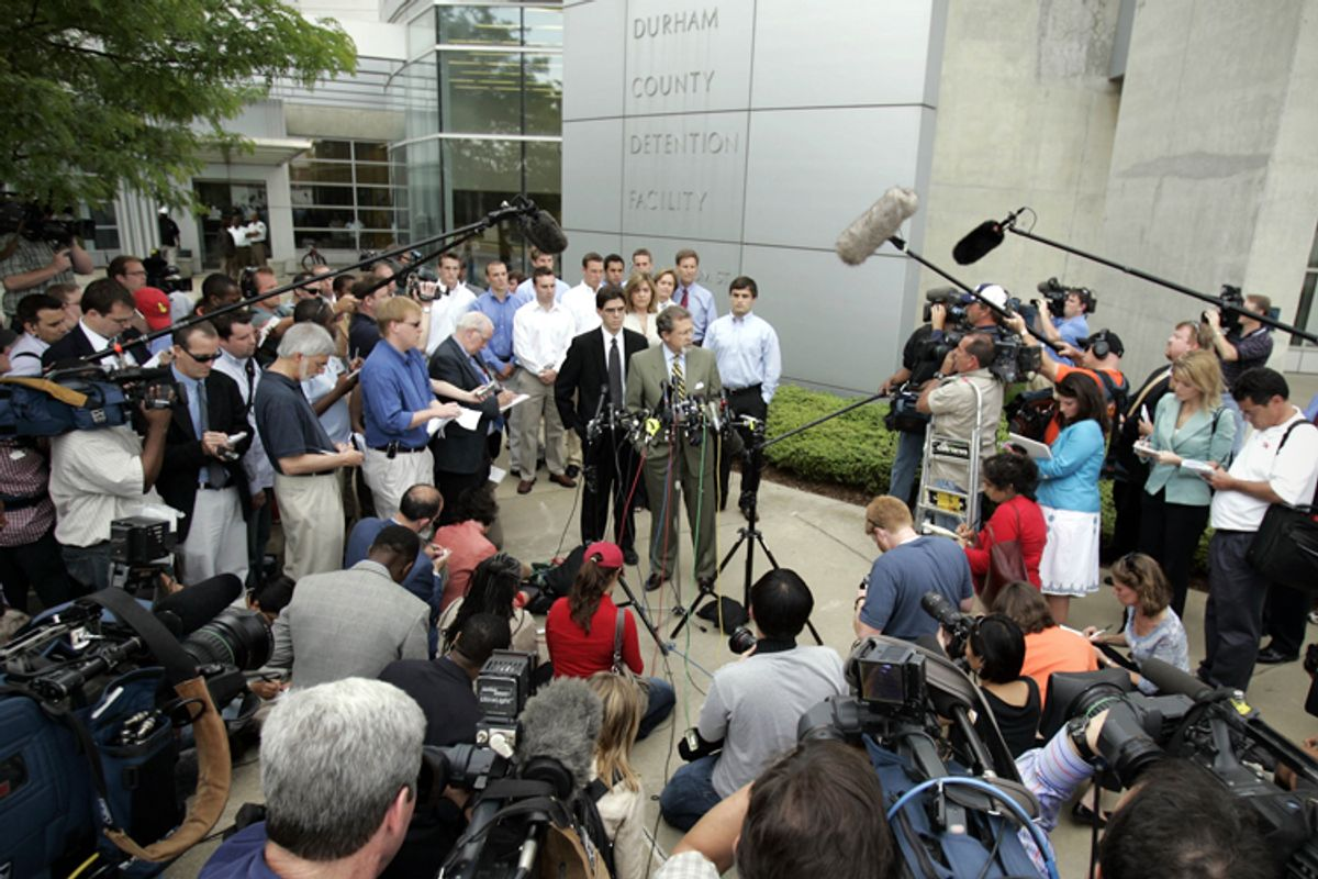 Joe Cheshire, attorney, at podium, and David Evans, senior captain of the Duke lacrosse team, right, make a statement in front of the Durham County Detention Center, May 15, 2006.   (AP/Gerry Broome)