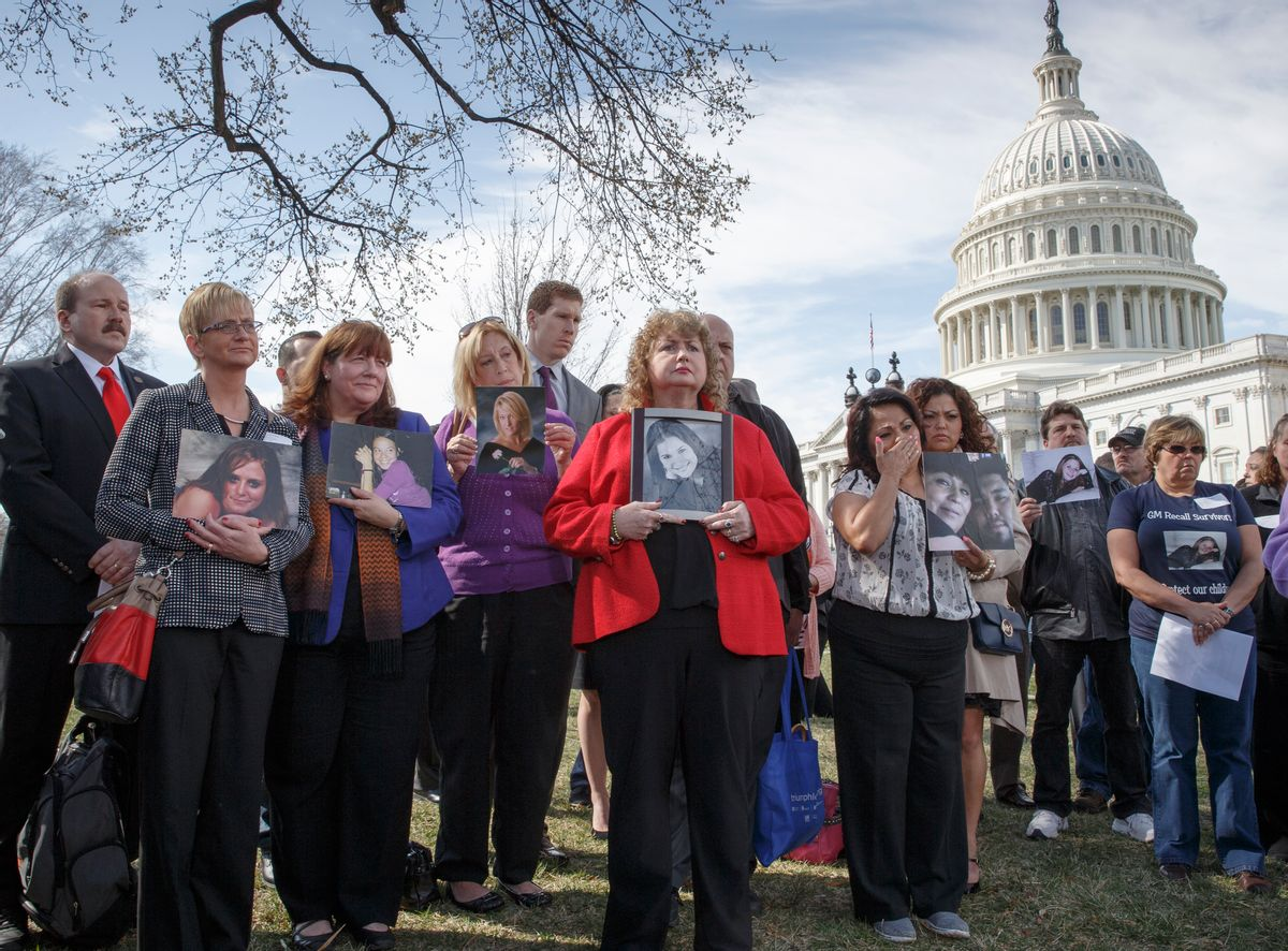 """Calling themselves """"GM Recall Survivors,"""" families of victims of a General Motors safety defect in small cars hold photos of their loved ones (AP)"""