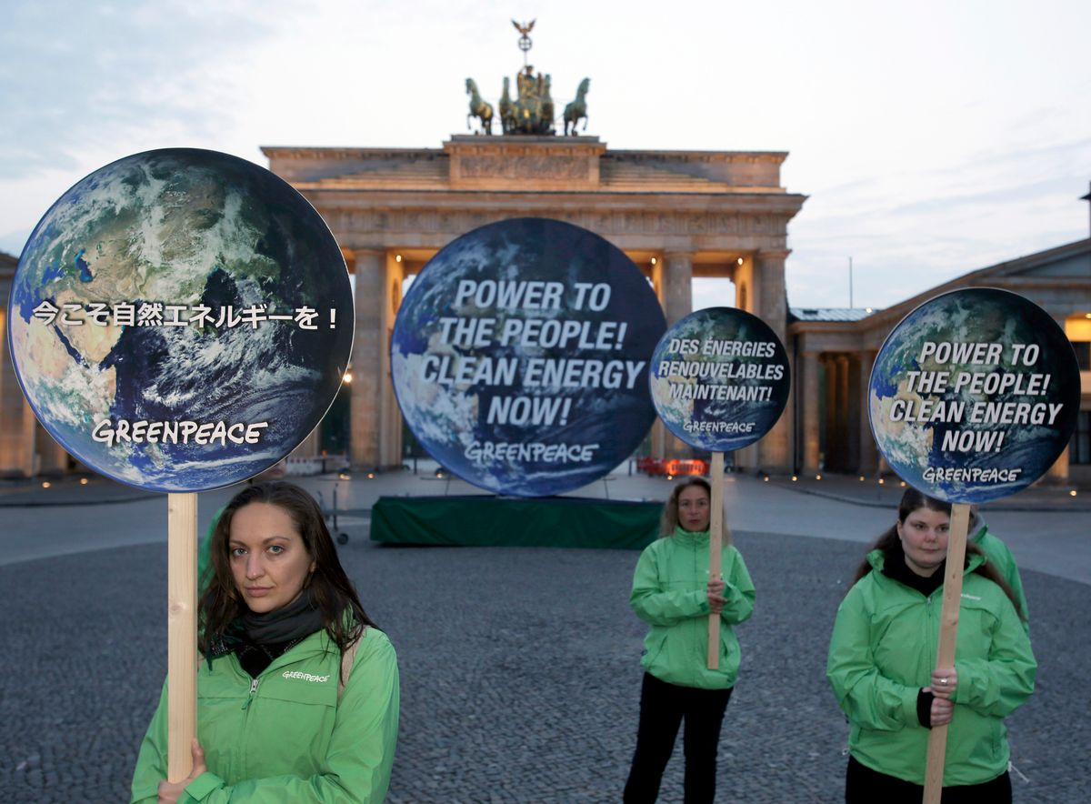 Activists of the international environmentalist organization Greenpeace pose with posters in front of the Brandenburg Gate in Berlin, Germany, Sunday, April 13, 2014  to support clean energy. After a one week meeting of the Intergovernmental Panel on Climate Change in Berlin the final document which is released on Sunday is expected to say that a global shift to renewable energy from fossil fuels like oil and coal are required to avoid potentially devastating sea level rise, flooding, droughts and other impacts of warming. (AP Photo/Michael Sohn) (Michael Sohn)