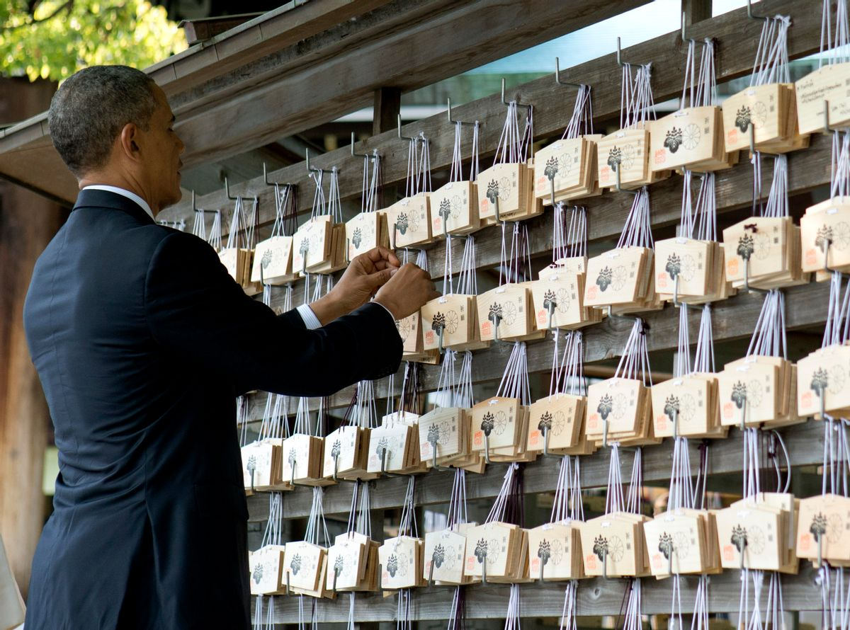 President Barack Obama places a prayer tablet on the Votive Tree as he tours the Meiji Shrine in Tokyo, Thursday, April 24, 2014. Opening a four-country swing through the Asia-Pacific region, Obama is aiming to promote the U.S. as a committed economic, military and political partner, but the West's dispute with Russia over Ukraine threatens to cast a shadow over the president's sales mission.(AP Photo/Carolyn Kaster) (Carolyn Kaster)