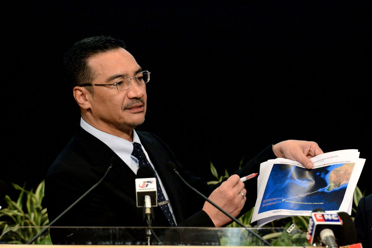 Malaysia's Defense Minister and acting Transport Minister Hishammuddin Hussein shows a printout of the latest satellite image of objects that might be from the missing Malaysia Airlines plane, at Putra World Trade Center in Kuala Lumpur, Malaysia, Wednesday, March 26, 2014. Hishammuddin said the objects were seen close to where three other satellites previously detected objects.  (AP Photo/Joshua Paul)   (Joshua Paul)