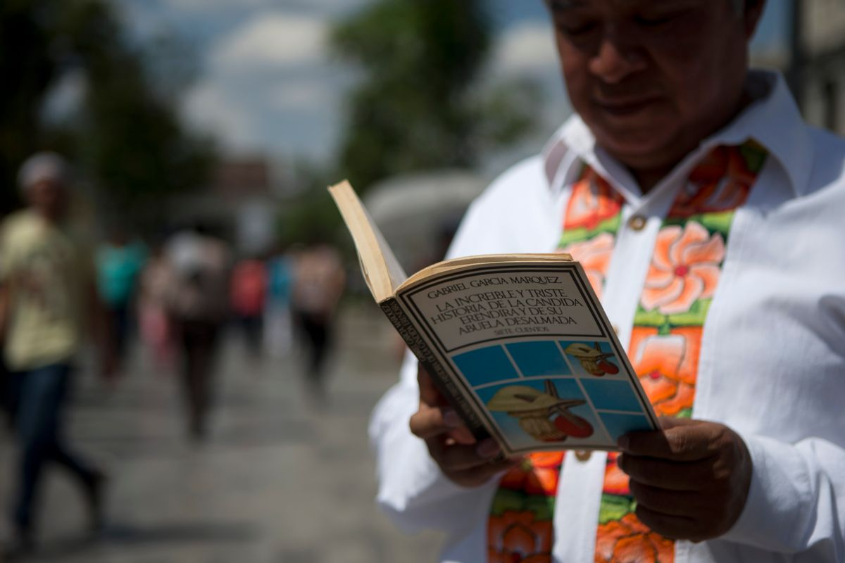 A man reads a book by Colombian Nobel Literature laureate Gabriel Garcia Marquez as he waits in line to pay his respects to the author at the Palace of Fine Arts in Mexico City, Monday, April 21, 2014. The ashes of  Garcia Marquez were taken Monday to Mexico City's majestic Palace of Fine Arts, where thousands of admiring readers began paying tribute to the Colombian Nobel laureate considered one of the greatest Spanish-language authors of all time.  (AP Photo/Rebecca Blackwell) (AP)