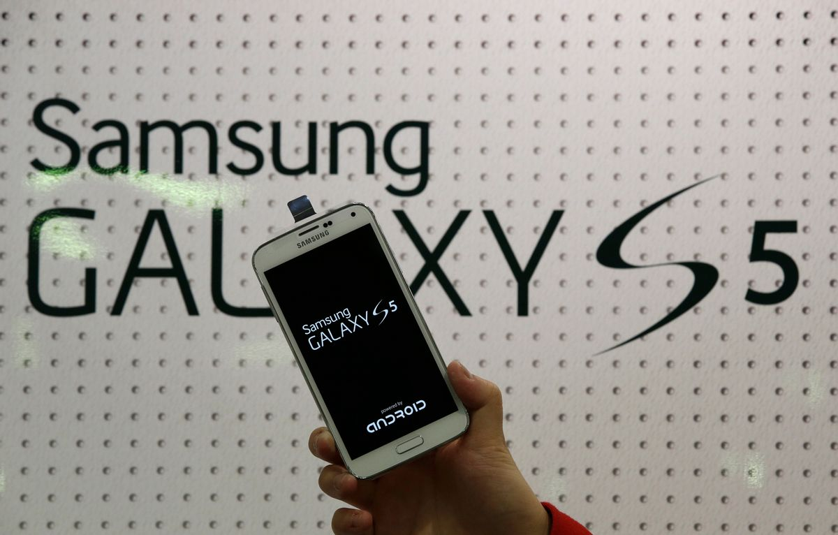 An employee shows Samsung's Galaxy S5 smartphone at a mobile phone shop in Seoul, South Korea, Thursday, March 27, 2014. The global launch of Samsung's latest smartphone is being upstaged by South Korean mobile network companies. SK Telecom, South Korea's largest mobile carrier, said it will start selling the Galaxy S5 on Thursday, two weeks before the scheduled sales launch on April 11. (AP Photo/Lee Jin-man)  (Lee Jin-man)