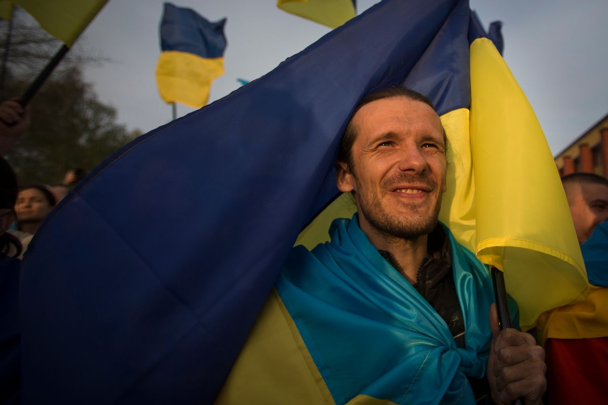 A man holds a Ukrainian national flag during a rally in support of a united Ukraine in Donetsk, Ukraine, Thursday, April 17, 2014. Defense Secretary Chuck Hagel says the U.S. will send nonlethal assistance to Ukraine's military in light of what he called Russia's ongoing destabilizing actions there. (AP Photo/Alexander Zemlianichenko) (AP)