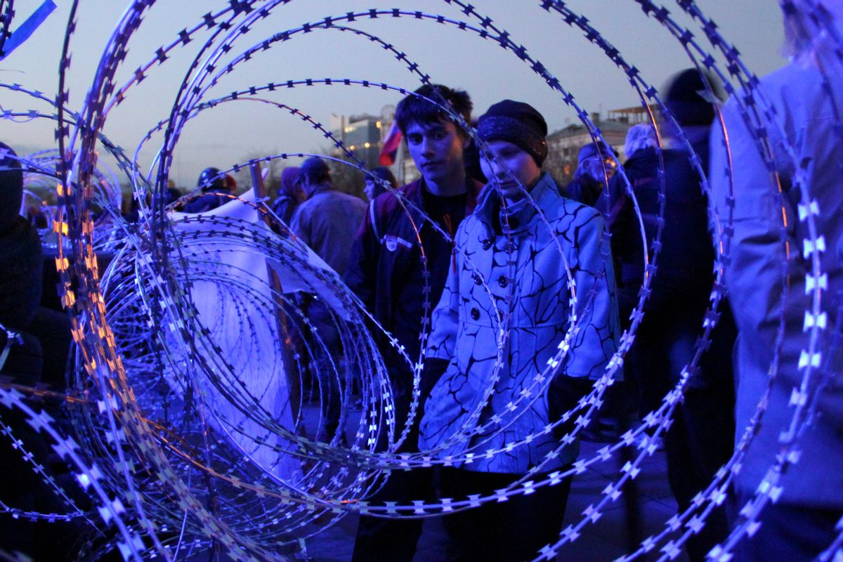 People gather near a barricade with razor wires at the regional administration building in Donetsk, Ukraine, late Monday, April 7, 2014. Outside the Donetsk building, a barricade of car tires and razor wire was built up to thwart police from retaking it. Interfax cited police in Donetsk as saying one armed group fired into the air and attempted to seize the regional state television broadcaster Monday but retreated after police and guards in the building also fired warning shots into the air. (AP Photo/Alexander Ermochenko) (AP)