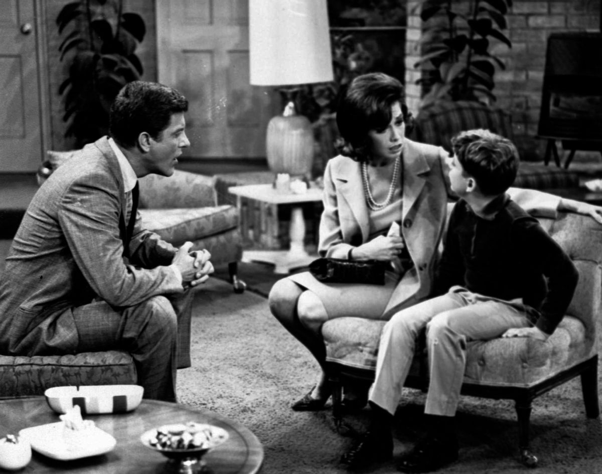 """FILE - In this 1965 file photo, from left, Dick Van Dyke, as Rob Petrie, and Mary Tyler Moore, as Laura Petrie, talk to Larry Matthews, who plays their son, Ritchie, on """"The Dick Van Dyke Show."""" Moore is being spotlighted in a new DVD collection called """"The Dick Van Dyke Show: Classic Mary Tyler Moore Episodes."""" The set gathers 20 episodes that dwell on the home life of Rob and Laura Petrie, putting the comic radiance of Moore on full display. (AP Photo/File) (AP)"""