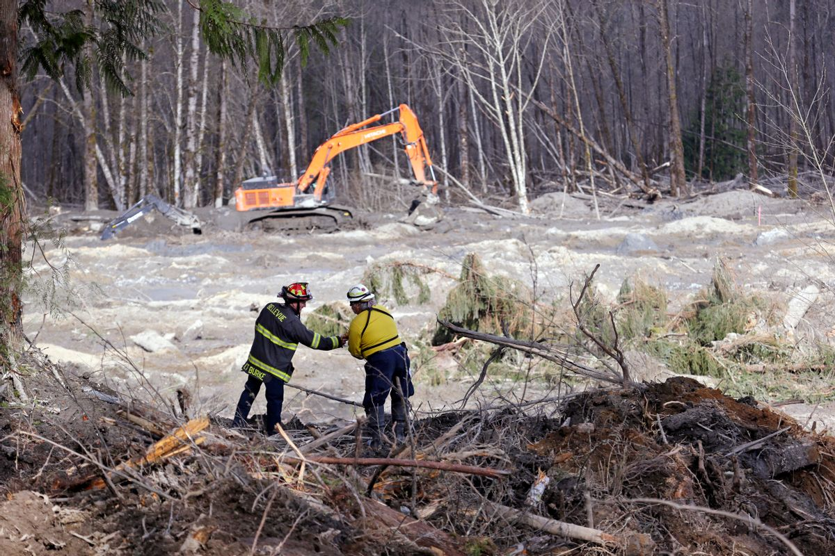 Bellevue, Wash., Fire Dept. Lt. Richard Burke, left, reaches across to shake hands with Benton County assistant fire chief Jack Coats as the two overlook the scene of a deadly mudslide Wednesday, April 2, 2014, in Oso, Wash. (AP Photo/Elaine Thompson)
