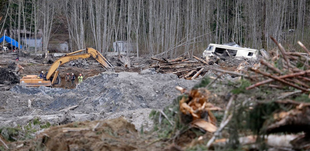 A demolished recreational vehicle lies in a debris field at the scene of a deadly mudslide nearly two weeks earlier nearby, Thursday, April 3, 2014, in Oso, Wash. (AP Photo/Elaine Thompson)
