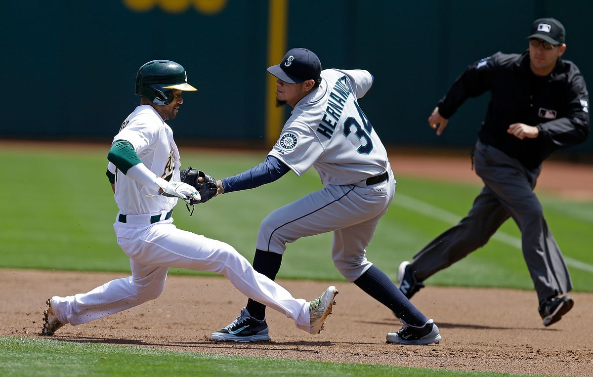 Seattle Mariners pitcher Felix Hernandez, right, tags out Oakland Athletics' Coco Crisp in a rundown between first and second base in the first inning of a baseball game Wednesday, May 7, 2014, in Oakland, Calif.      (AP/Ben Margot)