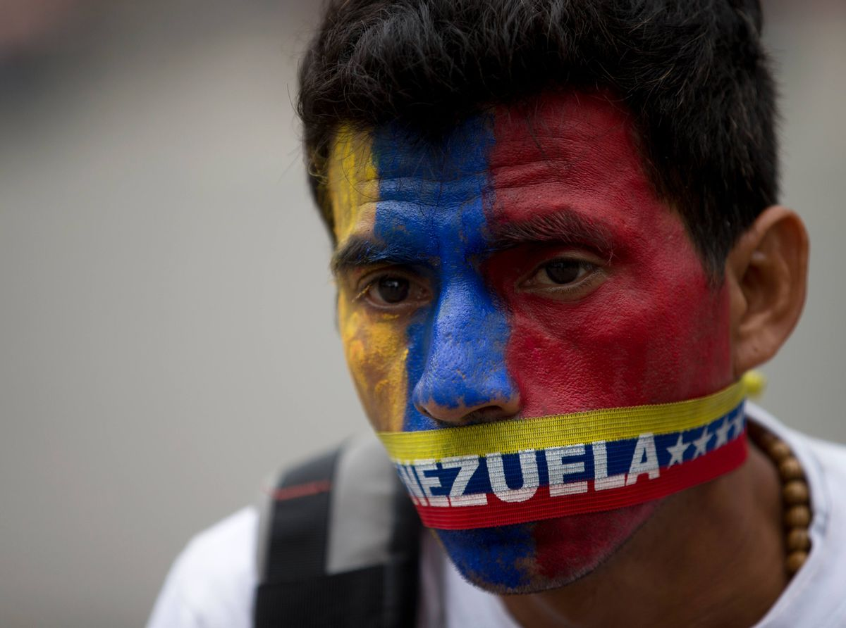 A man wears a narrow strip in the colors of Venezuela's flag over his mouth in protest of officials breaking up camps maintained by student protesters, in Caracas, Venezuela, Thursday, May 8, 2014. Hundreds of security forces broke up four camps maintained by student protesters, arresting more than 200 people in a pre-dawn raid. The camps of small tents were installed more than a month ago in front of the UN building and other anti-government strongholds in the capital to protest against President Nicolas Maduro's government. (AP Photo/Fernando Llano) (AP)