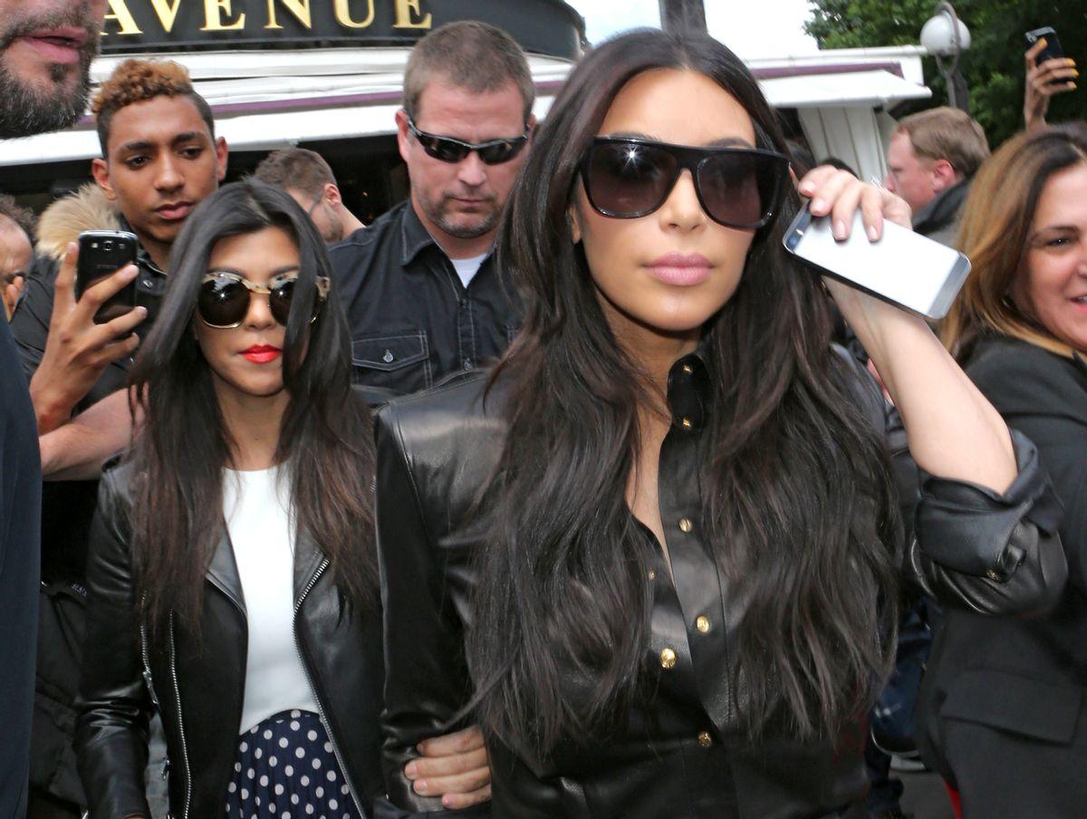Kim Kardashian, front and Kourtney Kardashian, left, leave at a restaurant in Paris, Thursday, May 22, 2014. (AP Photo/Jacques Brinon)
