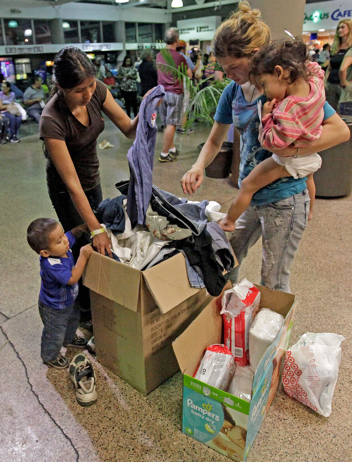 Women and children look through a box of cloths that were donated by volunteers at the Greyhound bus terminal, Thursday, May 29, 2014 in Phoenix.  About 400 mostly Central American women and children caught crossing from Mexico into south Texas were flown to Arizona this weekend after border agents there ran out of space and resources.  Officials then dropped hundreds of them off at Phoenix and Tucson Greyhound stations, overwhelming the stations and humanitarian groups who were trying to help. (AP Photo/Rick Scuteri) (AP)