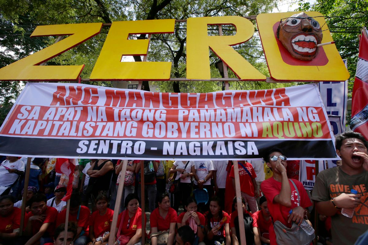 Workers shout slogans as they hold a rally near the Presidential Palace to mark the Labor Day celebrations on Thursday, May 1, 2014 in Manila, Philippines. Various labor groups nationwide held protests, mostly to demand wage hikes, better working conditions and an end to corruption in the government. The sign reads: Workers Have Zero Benefits In The Four Years of Capitalist Government of Aquino. (AP Photo/Bullit Marquez) (Bullit Marquez)