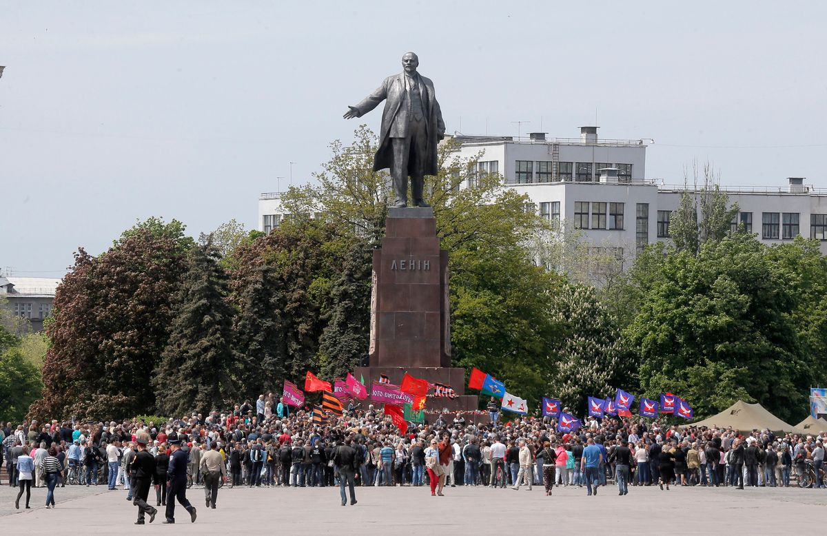 Ukrainians take part in a rally in front of a monument of Soviet revolutionary leader Vladimir Lenin, during a Victory Day celebration, which commemorates the 1945 defeat of Nazi Germany, in Kharkiv, Ukraine, Friday, May 9, 2014. Putin's surprise call on Wednesday for delaying the referendum in eastern Ukraine appeared to reflect Russia's desire to distance itself from the separatists as it bargains with the West over a settlement to the Ukrainian crisis. But insurgents in the Russian-speaking east defied Putin's call and said they would go ahead with the referendum. (AP Photo/Efrem Lukatsky) (AP)