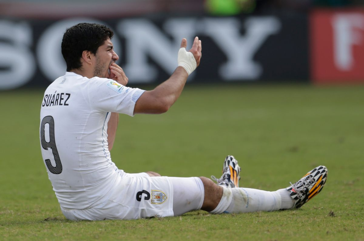 Uruguay's Luis Suarez holds his teeth after running into Italy's Giorgio Chiellini's shoulder during the group D World Cup soccer match between Italy and Uruguay at the Arena das Dunas in Natal, Brazil, Tuesday, June 24, 2014.       (AP/Petr David Josek)
