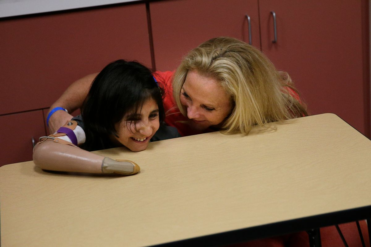 Shah Bibi Tarakhail, a six-year-old Afghan girl whose love of painting won the hearts of U.S. doctors who fitted her with a prosthetic, is tickled by her host mother, Ann Drummond, at Shriners Hospital for Children on Thursday, June 19, 2014, in Los Angeles. Shah Bibi Tarakhail, who lost her right arm and right eye when she picked up a grenade following a firefight between U.S. and Taliban forces in her village near the Pakistan border, returned to the United States on Thursday, after the group that sponsored her first visit said it learned her newfound celebrity made her a subject of death threats at home. (AP Photo/Jae C. Hong) (AP)