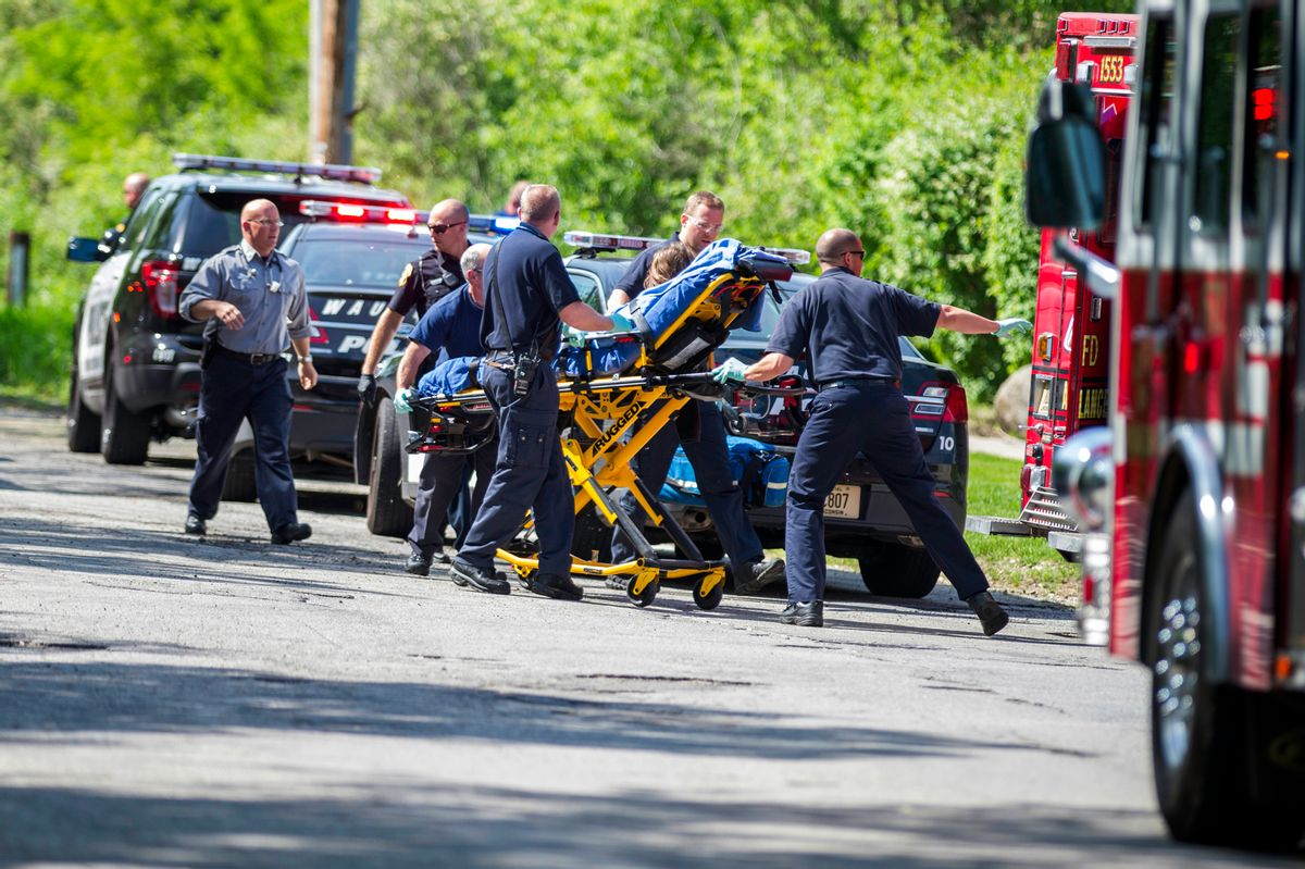In this Saturday, May 31, 2014 photo, rescue workers take a stabbing victim to the ambulance in Waukesha, Wis.  (AP/Abe Van Dyke)