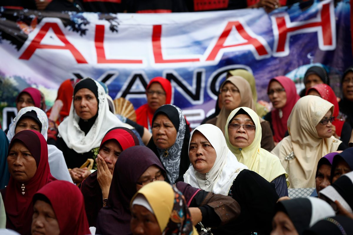"""Muslim women sit in front of a banner reading """"Allah"""" during a protest outside the Court of Appeal in Putrajaya, outside Kuala Lumpur, Malaysia, Monday, June 23, 2014. The Federal Court on Monday refused to grant leave to hear the appeal by the Catholic church over the word Allah in its newspaper.   (AP Photo/Vincent Thian) (AP)"""