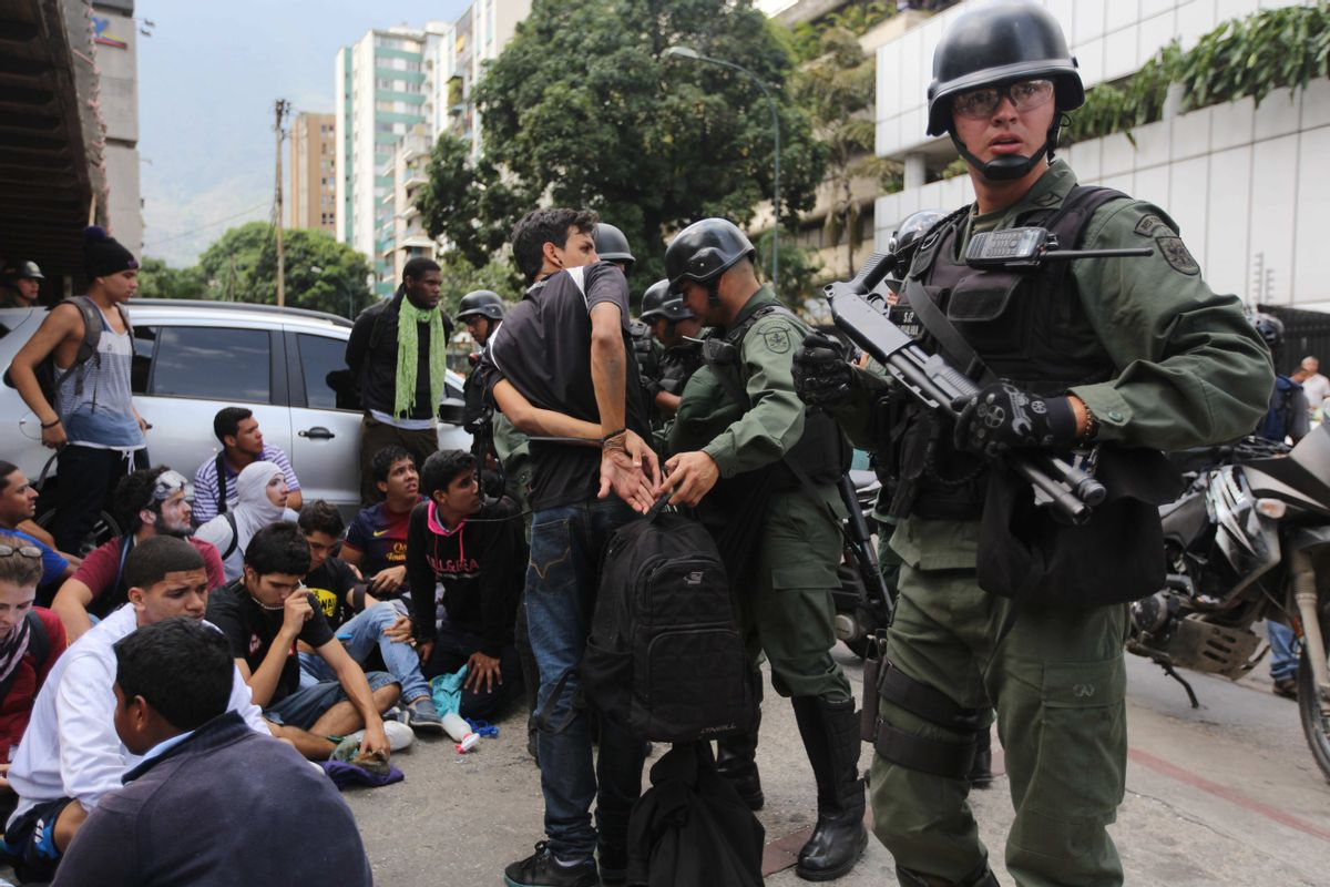 An anti-government demonstrator is handcuffed after he and others where detained by the Bolivarian National Guard, during clashes at a protest in Caracas, Venezuela, Wednesday, May 14, 2014.       (AP/Fernando Llano)