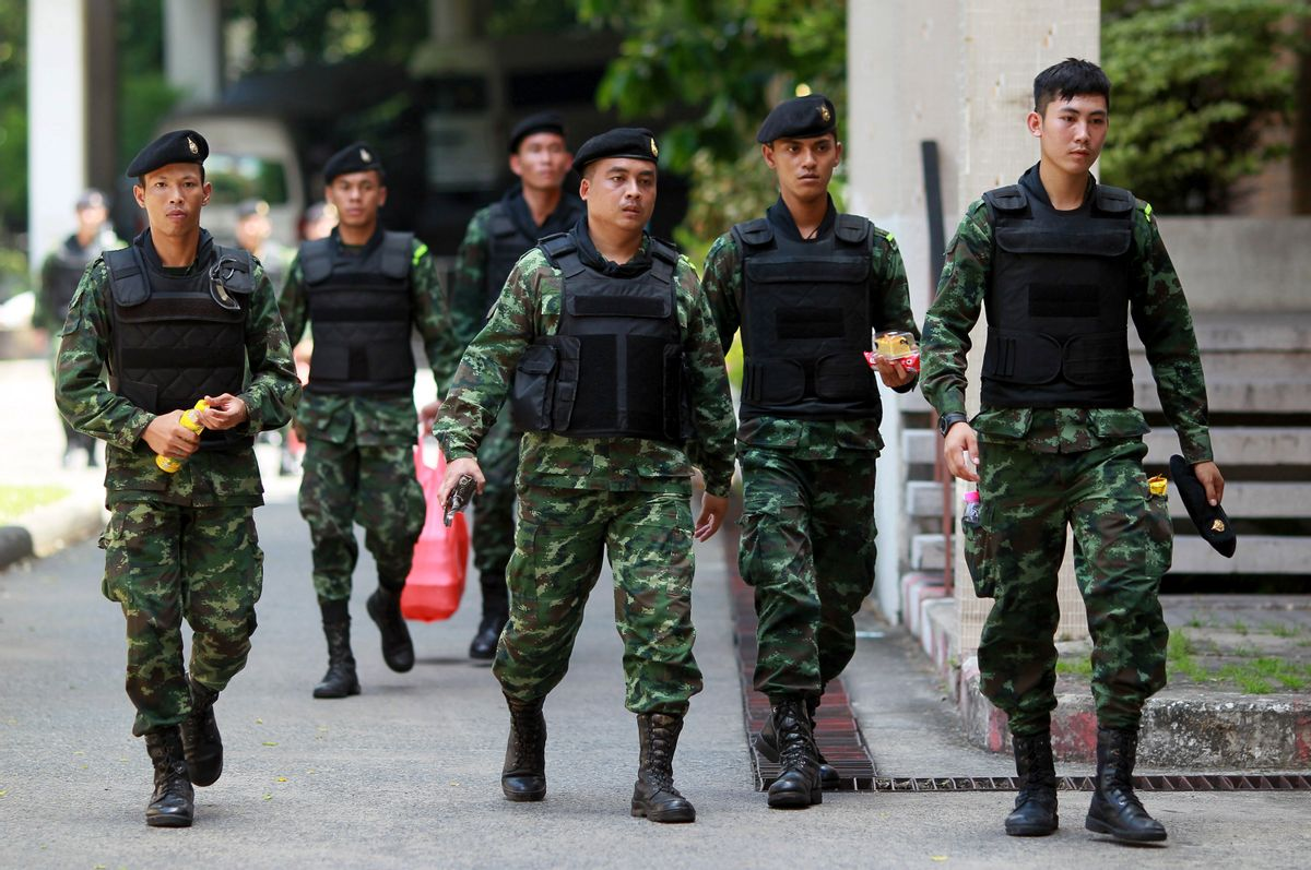 Thai soldiers walk after being deployed to guard in Bangkok's Victory Monument, Thailand Sunday, June 8, 2014.    (AP/Wason Wanichakorn)