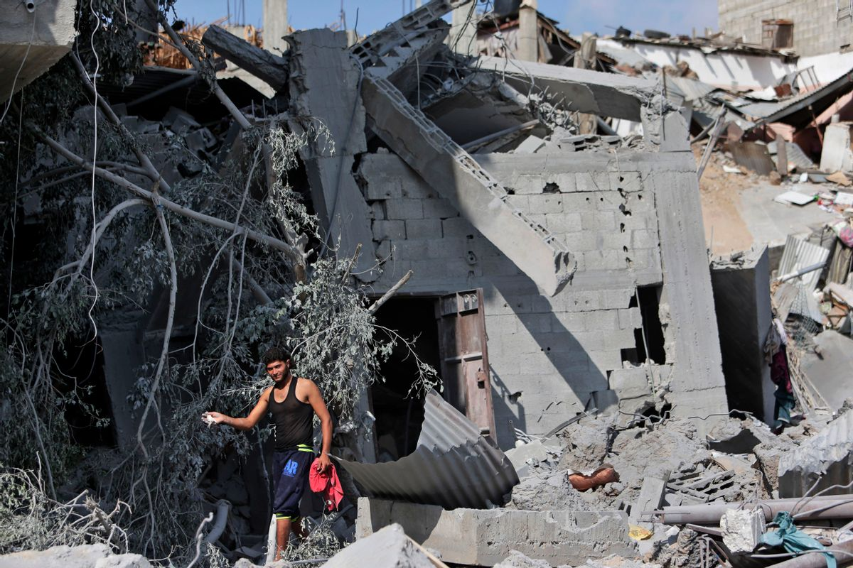 A Palestinian shows his pet bird which he managed to catch amid the rubble of houses destroyed by Israeli strikes in Beit Hanoun, northern Gaza Strip, Sunday, July 27, 2014. Hamas on Sunday agreed to observe a 24-hour humanitarian truce ahead of a major Muslim holiday after initially rejecting such an offer by Israel, as the two sides wrangled over setting the terms of a lull the international community hopes can be expanded into a more sustainable truce. (AP Photo/Lefteris Pitarakis) (AP)
