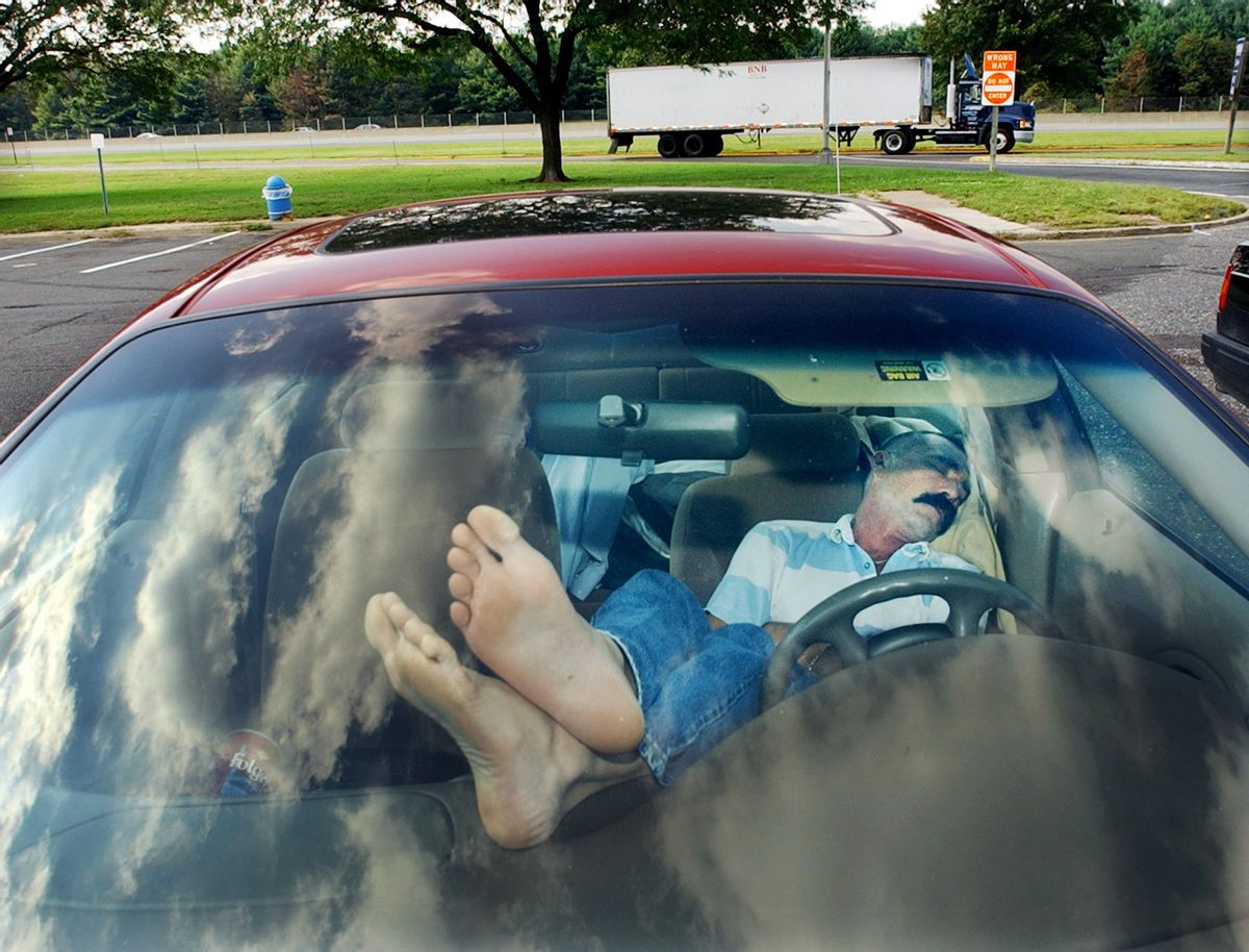 FILE - In this Sept. 25, 2003 file photo, an unidentified man rests his feet on the dashboard as he takes nap at a New Jersey Turnpike rest stop in Mount Laurel, N.J. The Centers for Disease Control and Prevention released its latest drowsy driving report on Thursday, July 3, 2014. According to a new survey, about 1 in 25 adults say they recently fell asleep while driving. (AP Photo/Daniel Hulshizer, File) (AP)