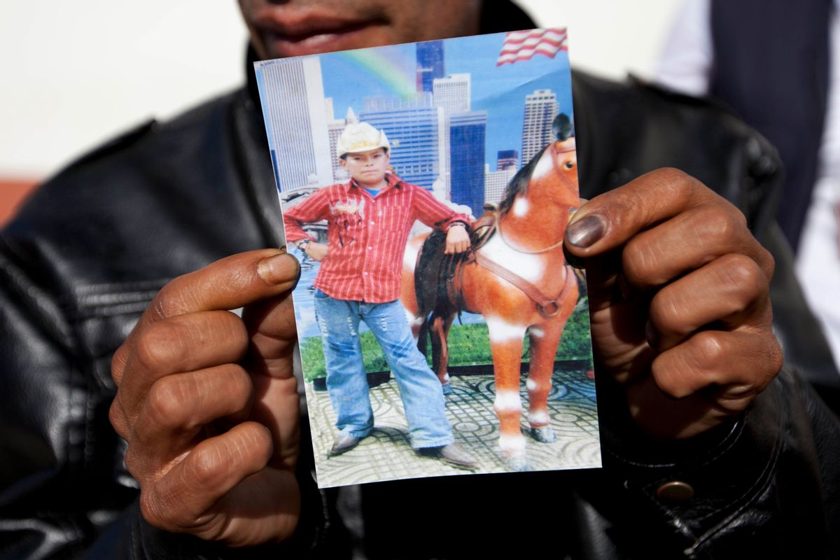 Francisco Ramos holds up a picture of his son, whose decomposed body was found in the Texas desert, as he waits for the arrival of his son's body, in Customs, in Guatemala City, Friday, July 11, 2014. The remains of Gilberto Francisco Ramos, the 15 year old boy who died in the Rio Grande Valley of South Texas, trying to reach the United States alone, was delivered to his family on Friday. (AP/Moises Castillo)