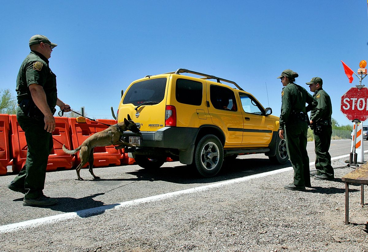 U.S. Border Patrol Senior Agent B.T. Hick and his dog Mirza, left, inspect a car at a check point outside Organ Pipe Cactus National Park in Why, Ariz., Wednesday, May 24, 2006. The detention of a prominent immigration activist at a Texas airport served as a reminder of the latitude the Border Patrol has in conducting checkpoints for drugs and immigrants in the country illegally at locations not on the border. (AP Photo/Matt York, File) (AP)