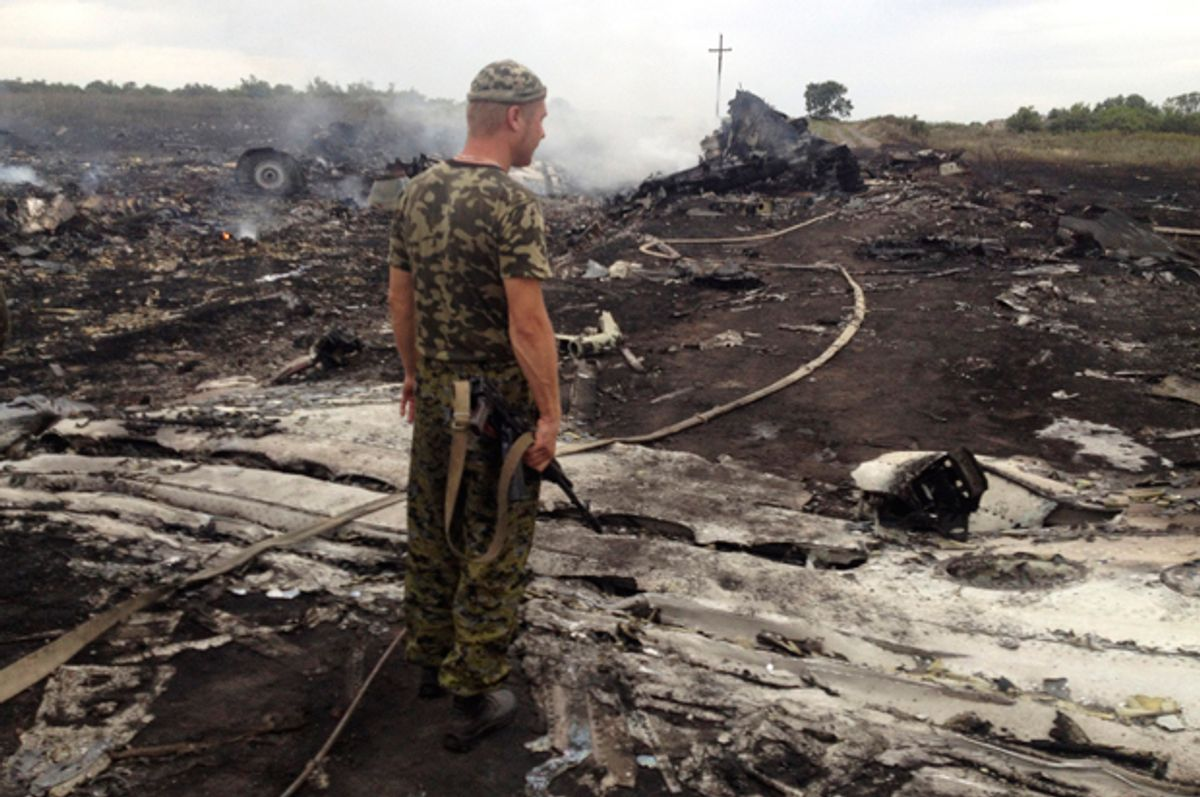 An armed pro-Russian separatist stands at a site of a Malaysia Airlines Boeing 777 plane crash in the settlement of Grabovo in the Donetsk region, July 17, 2014.           (Reuters/Maxim Zmeyev)