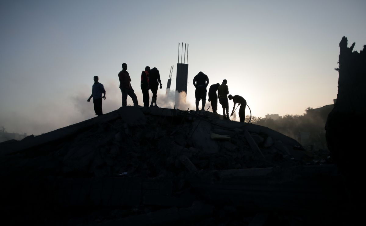 Palestinians try to salvage what they can of their belongings from the rubble of a house destroyed by an overnight Israeli airstrike in Gaza City Tuesday, July 8, 2014. Israel launched what could be a long-term offensive against the Hamas-ruled Gaza Strip on Tuesday, the military said, striking at least 50 sites in Gaza by air and sea and mobilizing troops for a possible ground invasion in order to quell rocket attacks on Israel. (AP Photo/Khalil Hamra) (AP)