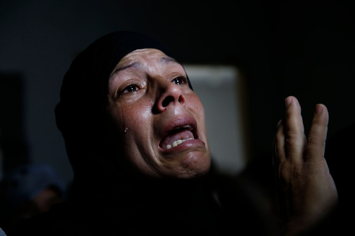 A Palestinian mourner cries in a house after the bodies of Mousa Abu Muamer, 56, and his son Saddam, 27, who were killed in an overnight Israeli missile strike at their house in the outskirts of the town of Khan Younis, southern Gaza Strip, were brought in for their funeral, Monday, July 14, 2014. Saddam's wife, Hanadi, 27, was also killed in the attack. (AP Photo/Lefteris Pitarakis) (AP)