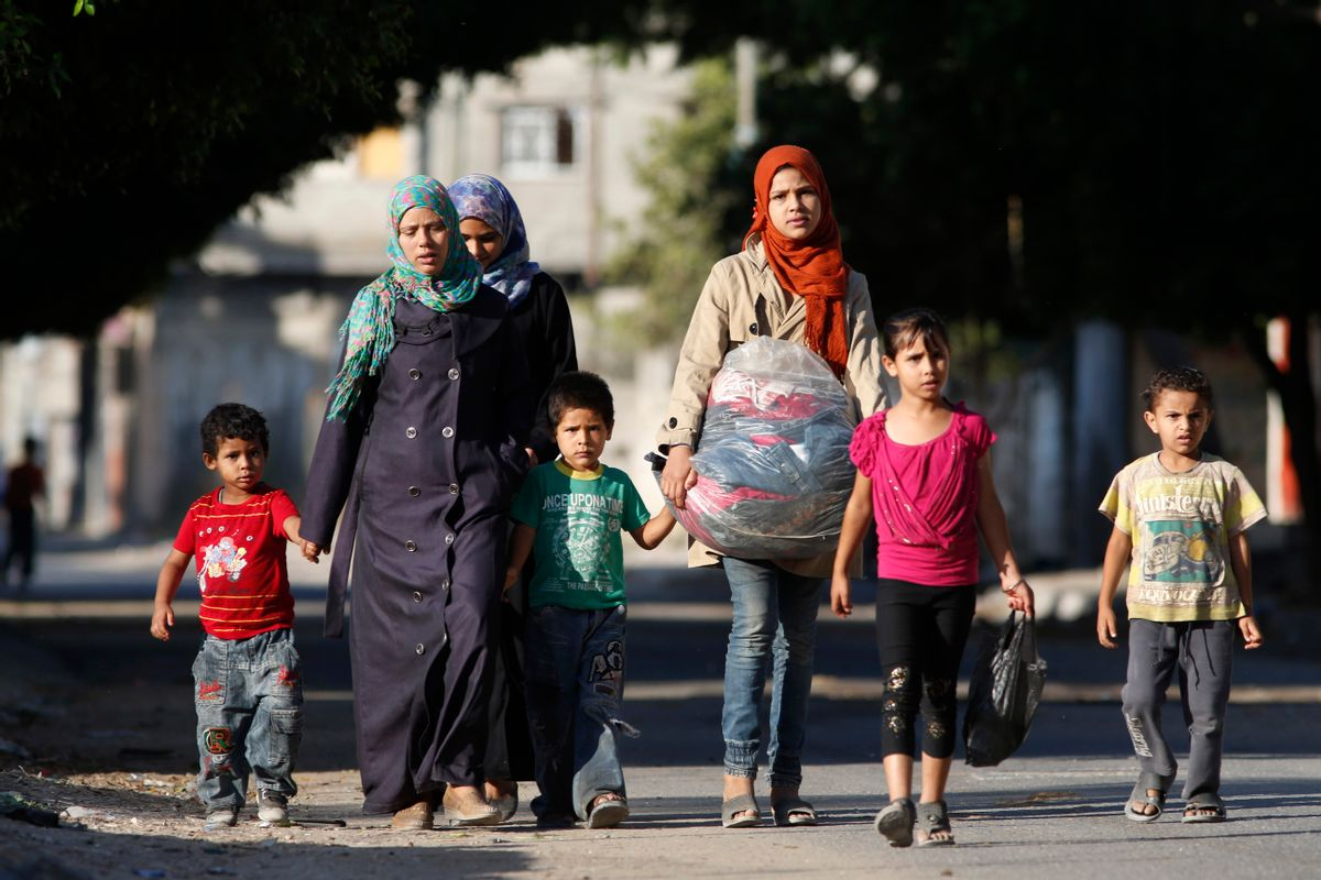 Palestinians flee their homes in the Zeitoun neighbourhood of Gaza City, after Israel had airdropped leaflets warning people to leave the area, Wednesday, July 16, 2014.   (AP/Lefteris Pitarakis)