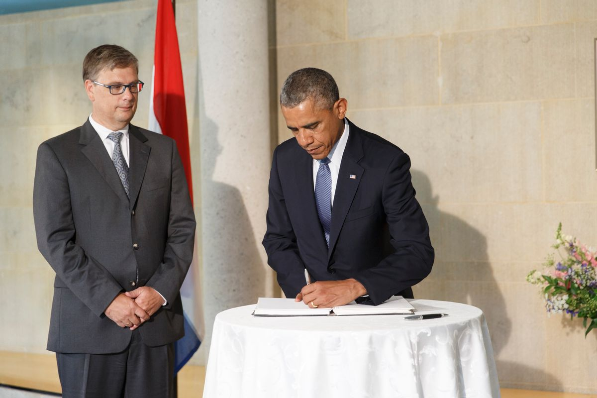 President Barack Obama visits the Dutch Embassy in Washington to sign a book of condolence, joined by Deputy Chief of Mission Peter Mollema, Tuesday, July 22, 2014. Most of the 298 people aboard the Malaysia Airlines plane that was shot down near the border between Ukraine and Russia were Dutch citizens. (AP Photo/J. Scott Applewhite) (AP)