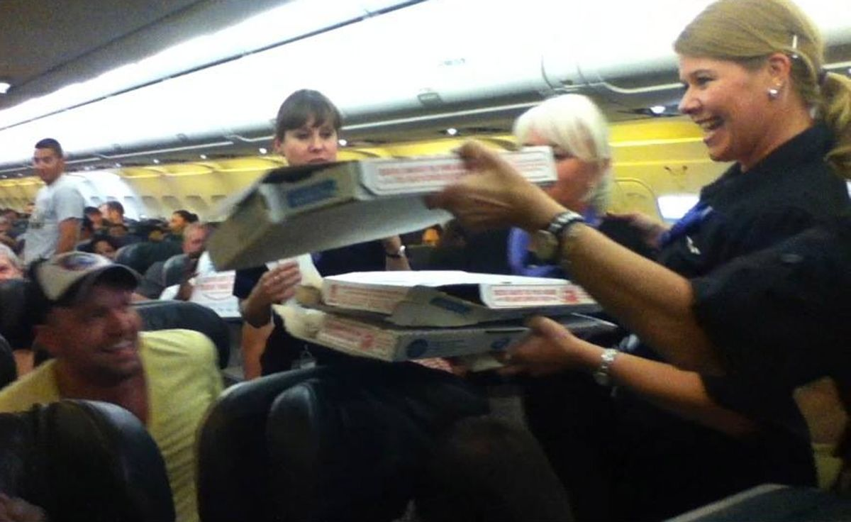 In this photo taken Monday, July 7, 2014, a Frontier Airlines flight attendant passes out pizza to passengers aboard a Denver-bound flight diverted to Cheyenne, Wyo. The airplane pilot treated his passengers to the pizza after they were diverted. (AP Photo/Logan Marie Torres)   (AP)